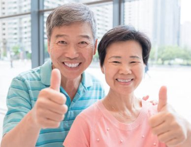 old couple smile and show thumb up to you